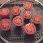 tomatoes on screen ready for drying in the oven