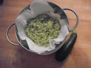 Shredded zucchini in colander with whole zucchini along side