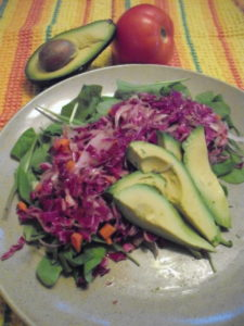 cabbage salad on a bed of spinach with sliced avocado and tomato