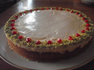 Cheesecake Cockaigne with pistachio dust trim and pomegranate seed decoration.