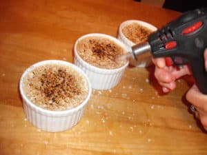 demonstration of torch to caramelize the top of pudding