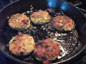 veggie fritters frying in cast iron skillet
