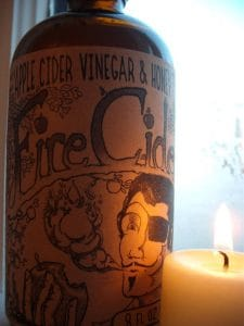 bottle of Fire Cider next to candle