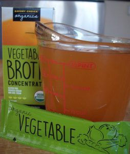 box , pouch and cup full of Savory Choice Vegetable Broth Concentrate