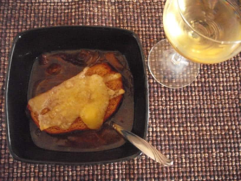 bowl of French onion soup with bread and cheese topper and glass of white wine