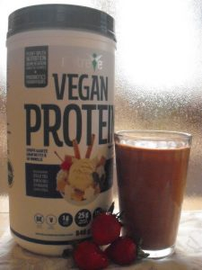 Natreve Wellness Vegan Protein powder with smoothie and strawberries