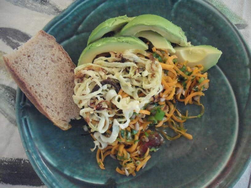 plate of curly carrot salad with roasted kohlrabi ribbons, avocado slices and piece of sourdough bread