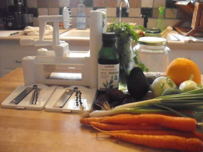 ingredients and spiralizer used to make the curly carrot salad