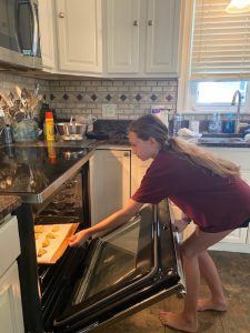 Hayley places cookies in the oven