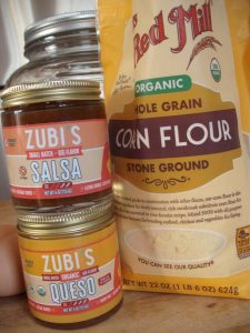 Jars of Zubi's salsa nd queso with a bag of Bob's Red Mill Organic Corn Flour