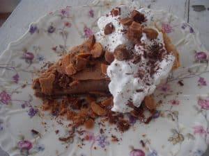 Chocolate Custard Pie slice with whipped cream, toasted hazelnuts and chocolate shavings